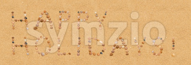 Happy Holidays! Written in sand using single seashells at the beach. Holiday concept.