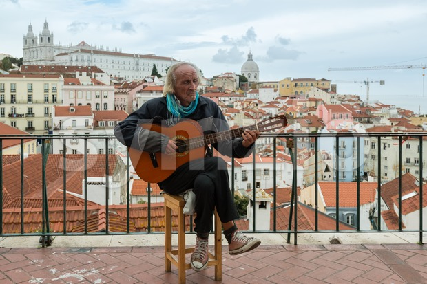 LISBON, PORTUGAL - OCTOBER 18, 2015: Typical Fado musician singing to his guitar in front of the district of Alfama, ...