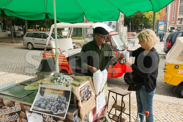LISBON, PORTUGAL - OCTOBER 19, 2015: A typical chestnut vendor in the streets of Lisbon offering freshly roasted chestnuts to ...