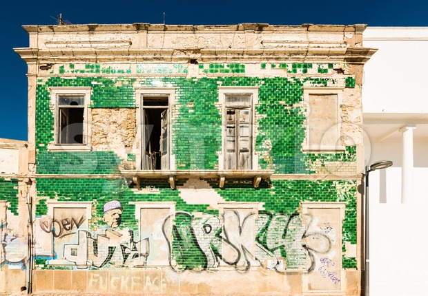 Albufeira, Portugal - October 22, 2015: Abandoned apartment building with stained green tiled walls, broken windows and graffiti tags next ...
