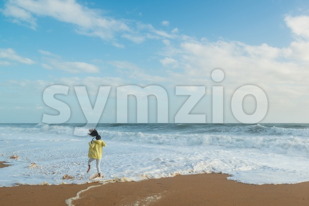 Albufeira, Portugal - October 17, 2015: Adorable girl jumping in the waves on the blue sea shore of Albufeira in ...