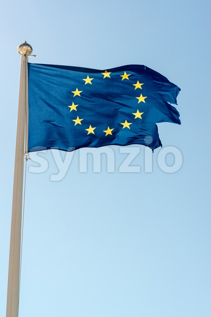 Rundown blue flag of the European Union against great blue sky. The flag is torn off at the side, maybe ...