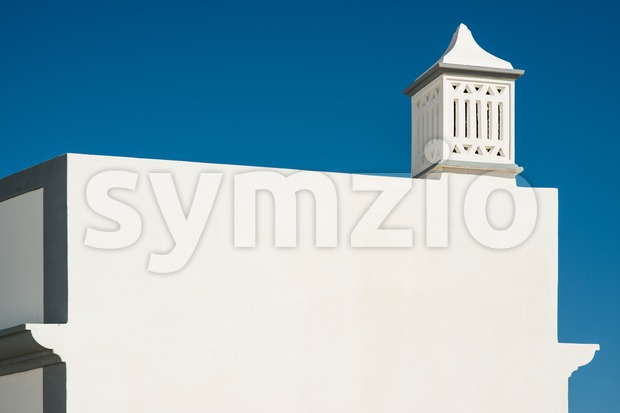 Traditional Portuguese chimney on top of a white building against great blue sky