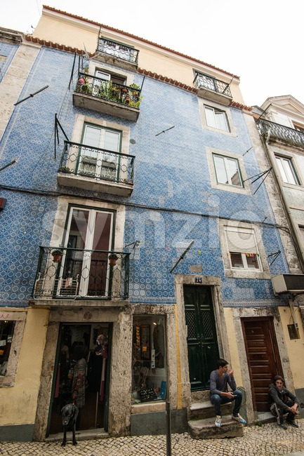 Lisbon, Portugal - October 19, 2015: Typical Lisbon street scene in an old narrow small street with tiled facades, small ...