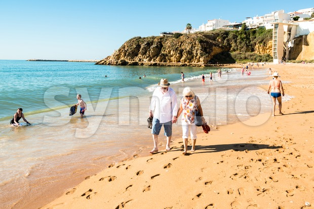 Happy senior couple walking together on a beach Stock Photo