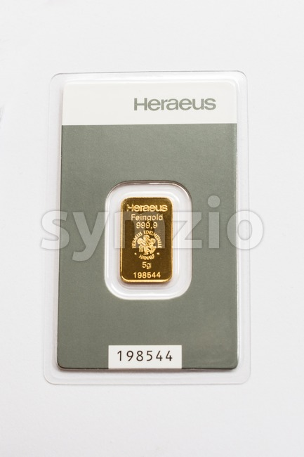 Moensheim, Germany - May 1, 2016: A tiny gold bar (5 grams) in its packaging by German manufacturer Heraeus. Due ...