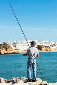 Angler on autumn sea coast Stock Photo