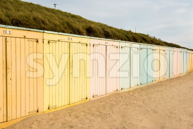 Lonely colorful beach lockers on a Dutch beach in sunset