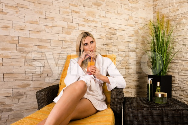 Gorgeous woman relaxing on a sunbed is drinking a cocktail in a short white bathrobe in a health spa with ...