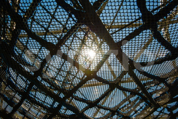 Abstract plastic and metal net texture against bright sunlight - concept for technology meeting nature or artificial social networks