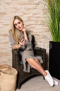 Gorgeous woman using mobile phone in a waiting area Stock Photo