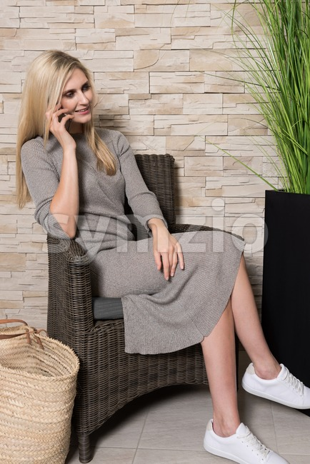 Gorgeous woman talking on mobile phone in a waiting area Stock Photo