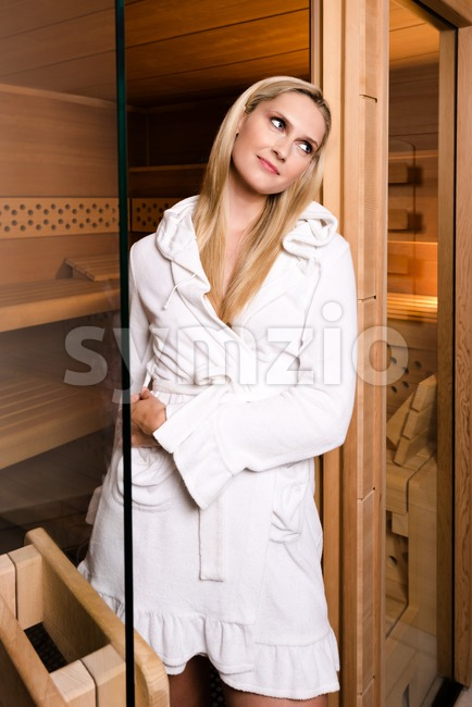 Attractive woman wearing a short white bathrobe is posing while leaving the sauna through a partly opened glass door