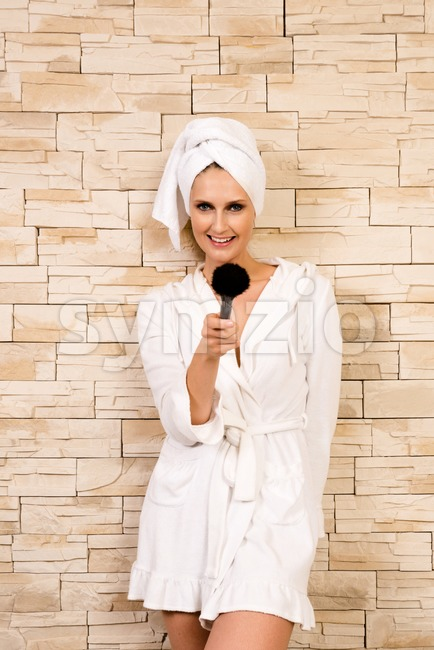 Joyful portrait of a gorgeous woman pointing with make-up brush towards the viewer in a short white bathrobe in front ...