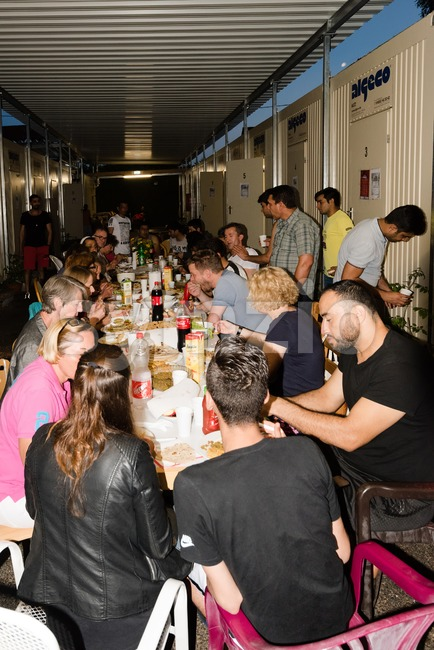 Muslim refugees and German volunteers sit together eating dinner during Ramadan fasting month Stock Photo