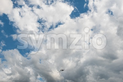 Airplane flying high in dramatic clouds Stock Photo