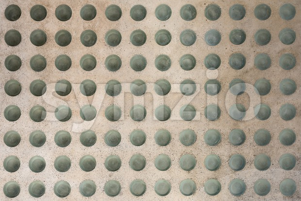 Abstract texture of a concrete floor with round glass inlets as seen from above
