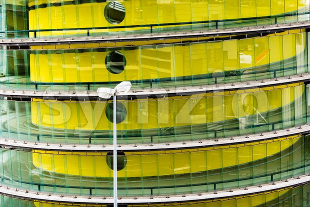 Ramp of a modern carpark building painted in bright yellow with reflections of surrounding parking areas