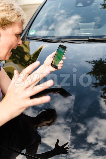 Pedestrian being hit by car while playing Pokemon Go on her smartphone Stock Photo