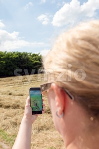 Playing Pokemon Go in the fields Stock Photo