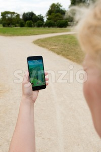 Playing Pokemon Go in the park Stock Photo