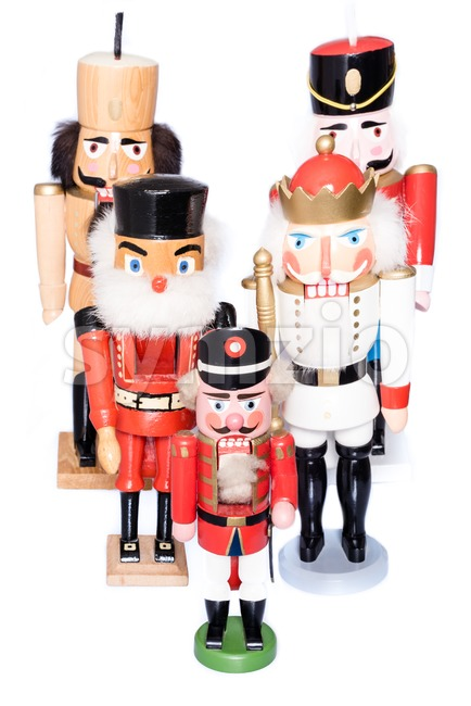 Army of nutcrackers - five antique wooden figurines in a studio shot on white background