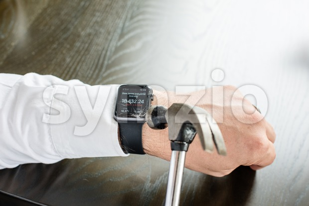 Businessman breaking Apple Watch with hammer Stock Photo