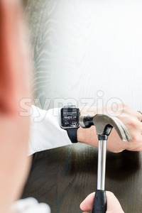 Businessman breaking Apple Watch with a hammer Stock Photo