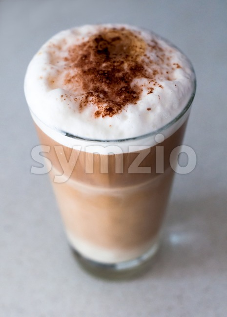 Cafe - Coffee Latte with cacao powder in a tall glass on bright background