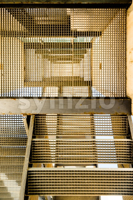 Abstract image of industrial stairs as seen from below forming a geometric pattern