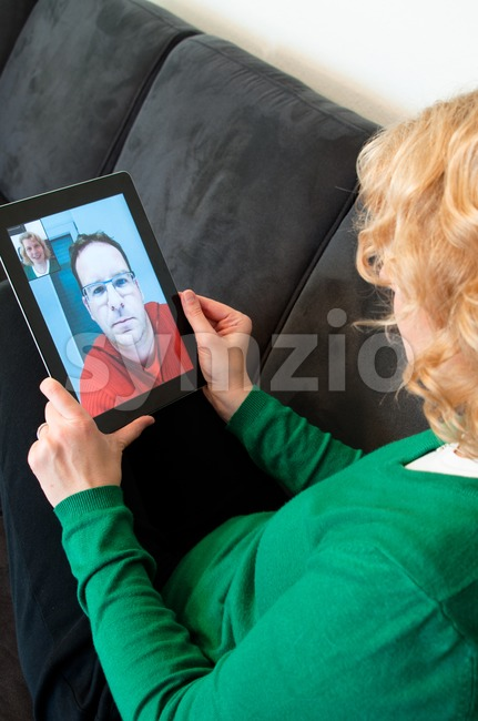 Middle-aged woman using video telephony on digital tablet pc