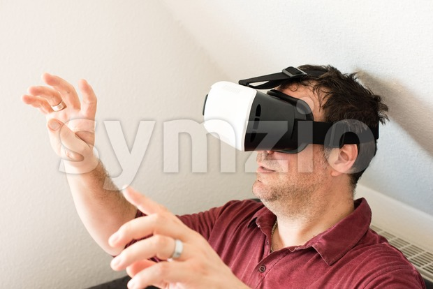 Man resting on sofa wearing VR headset glasses Stock Photo