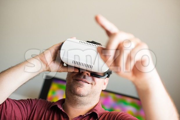 Caucasian man wearing VR headset glasses in front of tv screen making gestures with copy space for your text