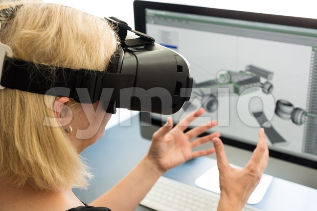 Female engineer working on computer creating a racecar using VR virtual reality glasses. Concept for women in hightech jobs.