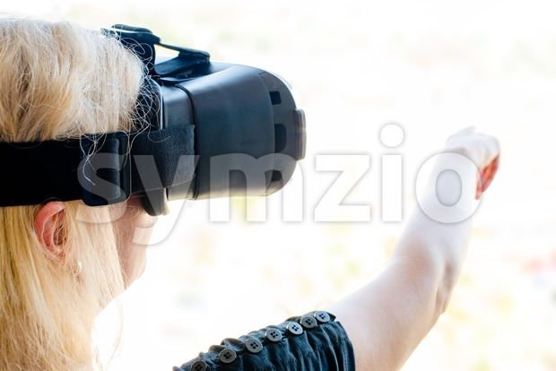 Woman using virtual reality glasses in a bright environment making gestures. New technology concept - the background can be replaced ...