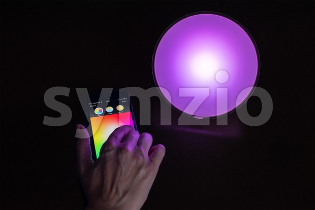 Female hand using Apple iPhone to control a Philips Hue smart home light Stock Photo
