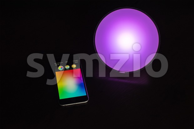 Apple iPhone being used to control a Philips Hue smart home light Stock Photo