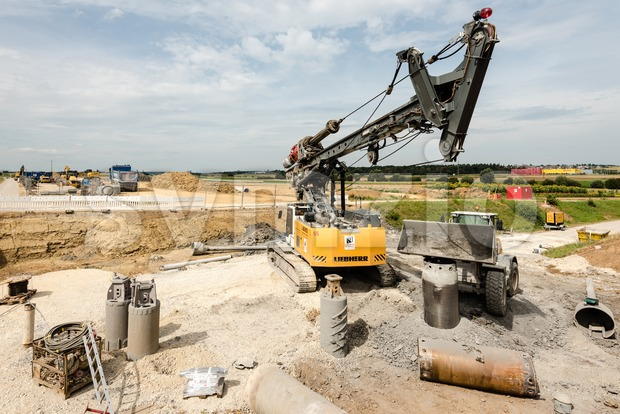 Large rotary drill and excavator on construction site Stock Photo