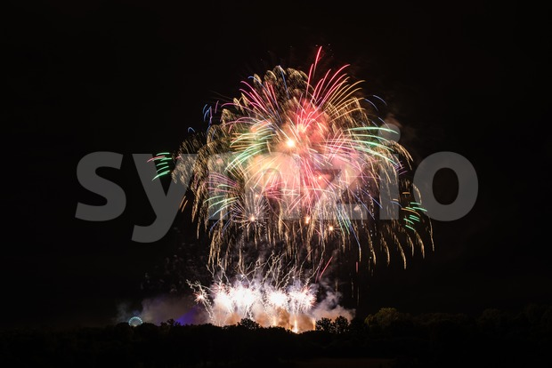 Huge colorful fireworks with ferries wheel to the left - celebrating New Year or other festivities - abstract holiday background ...