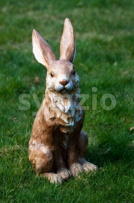Easter decoration: Clay rabbit sitting in grass field