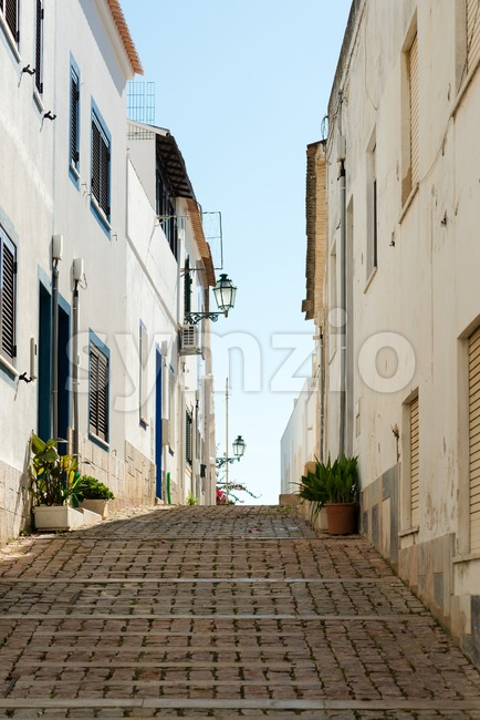 Typical narrow streets of Portugal with white houses