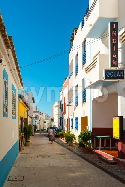 Albufeira, Portugal - October 22, 2015: Colorful Portuguese facades with Indian restaurant sign on a sunny day in Albufeira in ...