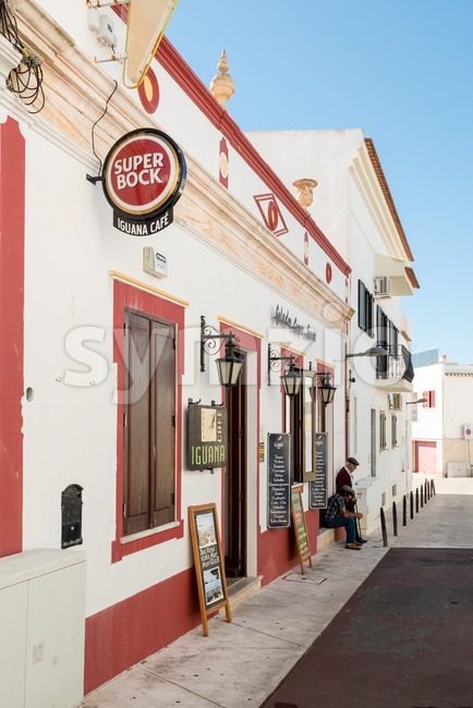 Albufeira, Portugal - October 22, 2015: Cozy Portuguese facades with cafe and elderly inhabitants sitting in the shadow on a ...