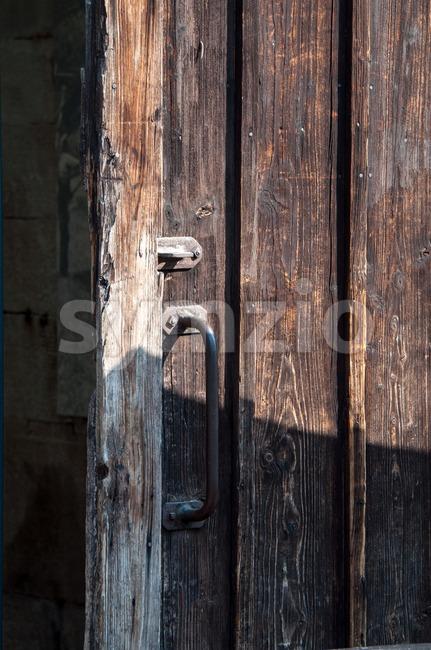 Rustic wooden barn door with rusty metal handles