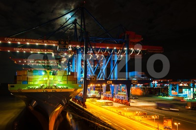 Large container ship at the Container Terminal Altenwerder in Hamburg at night Stock Photo