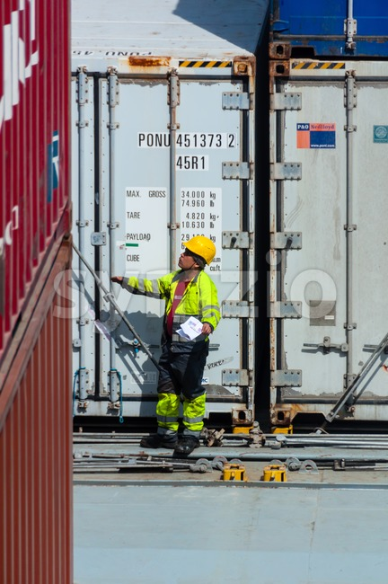 worker supervising container uploading at dock Stock Photo