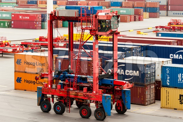 Straddle carrier is waiting to pick up containers at the Buchardkai Container Terminal in Hamburg Stock Photo