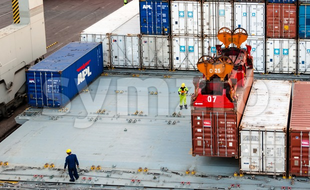 workers supervising container uploading at dock Stock Photo