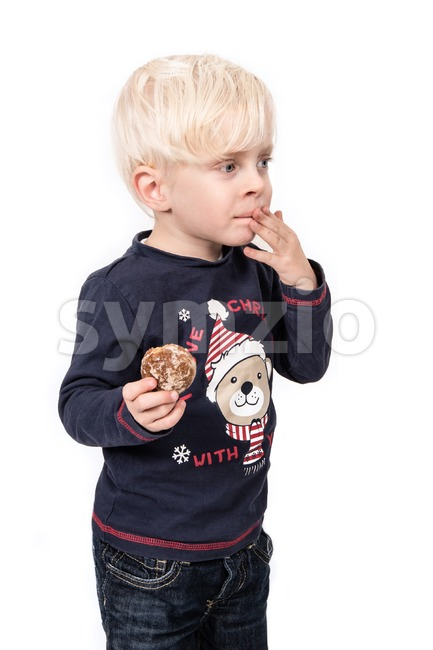 Magic of Christmas. Portrait of a cute boy eating a Christmas cookie on a white background