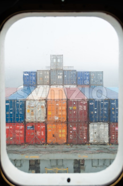 View throught the porthole of a container ship Stock Photo